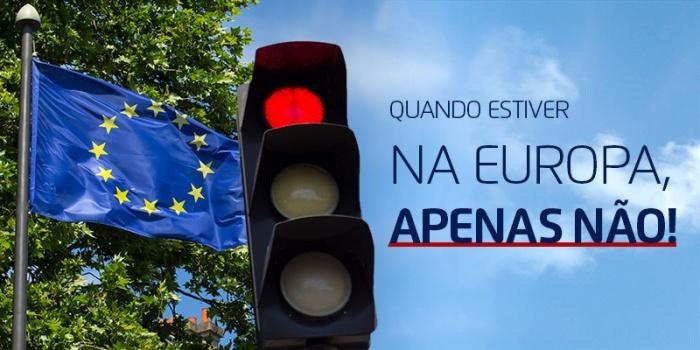 EU flag near red traffic light under blue sky